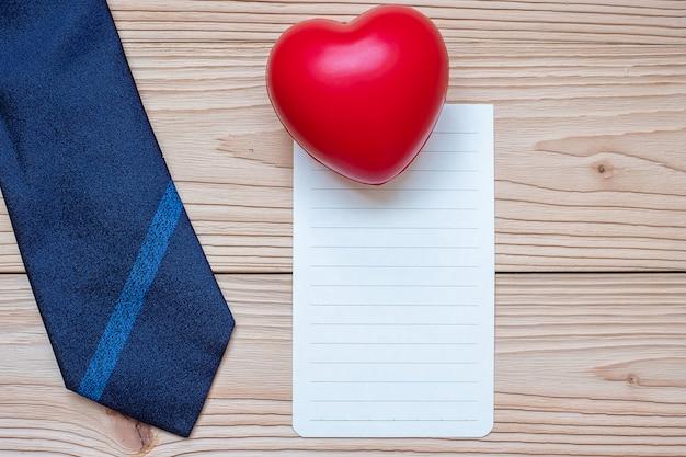 Carte vide avec cravate bleue et forme de coeur rouge sur bois