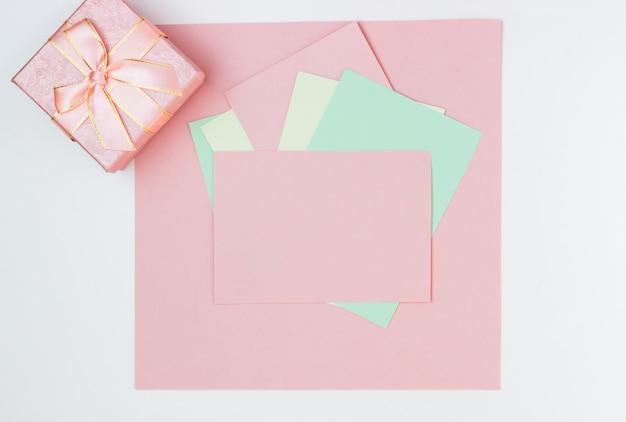Carte vide rose, feuille pour l'écriture. disposition pour ajouter des étiquettes avec boîte-cadeau. vue de dessus, mise à plat, espace copie
