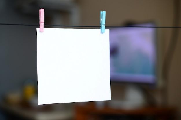 Carte vierge blanche sur corde, fond de bureau sombre