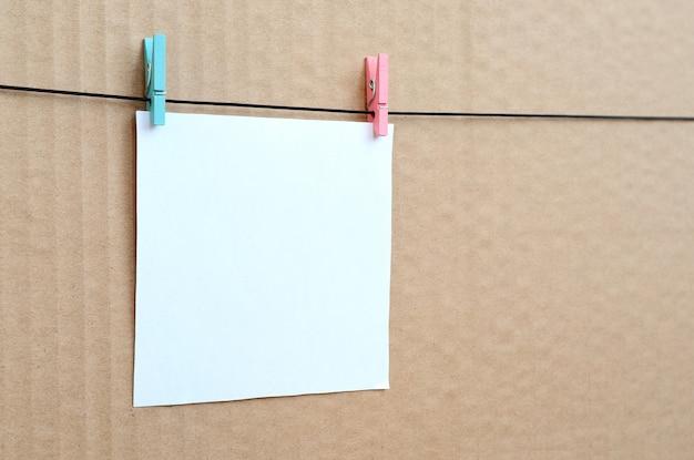 Carte vierge blanche sur la corde sur un fond de carton brun. rappel créatif, petite feuille de papier sur une pince à linge en bois, toile de fond mémo