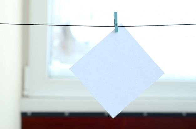 Carte vierge blanche sur corde, fond de vitre