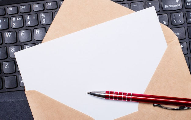 Carte vierge blanche avec enveloppe artisanale sur le bureau avec clavier d'ordinateur portable moderne et stylo bordeaux. aménagement plat du lieu de travail. espace de copie.