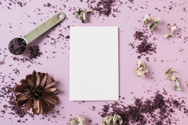 Carte vierge blanche avec fleur séchée et gommage sur fond rose