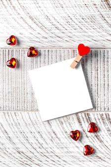 Carte vierge avec un coeur pour votre texte sur un fond en bois. concept de la saint-valentin, note d'amour. copiez l'espace.