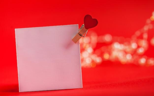Carte vierge avec un coeur pour votre texte sur un fond rouge concept de note d'amour pour la saint valentin