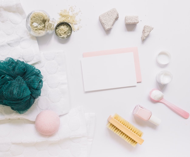 Carte vierge entourée de divers produits de spa sur fond blanc
