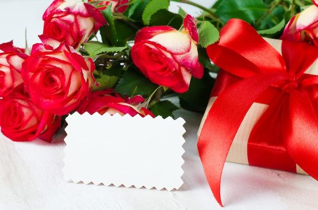 Carte vierge et présent et bouquet de roses rouges.