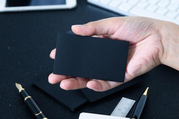 Carte de visite en blanc se maquillant en main sur le bureau de bureau floue nous utiliser informations de contact design templete