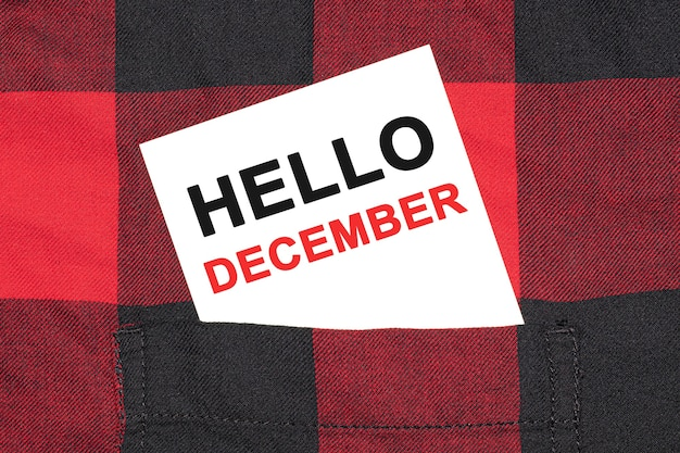 Carte De Visite Blanche Avec Texte Bonjour Décembre Se Trouve Dans La Manche D'une Chemise à Carreaux. Photo Premium