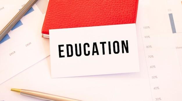 La carte de visite blanche avec le texte education se trouve à côté du porte-cartes de visite rouge. notion financière.