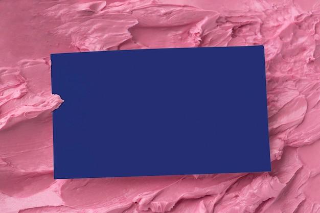 Carte de visite bleue sur la texture de glaçage rose