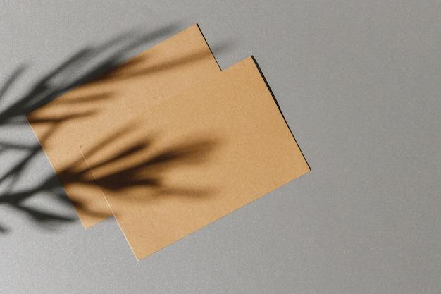 Carte de visite sur fond de papier avec ombre feuillage