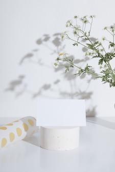 Carte de visite ou maquette d'invitation sur un piédestal avec une branche de camomille. créatif à la mode pour le secteur des cosmétiques