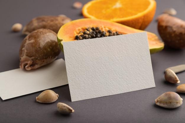 Carte de visite en papier blanc avec papaye coupée mûre, orange, coquillages