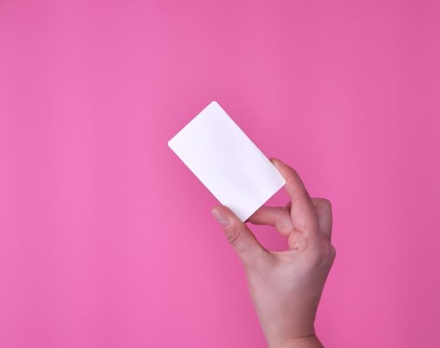 Carte de visite rectangulaire blanche vide dans une main féminine