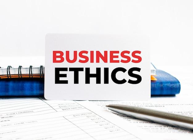 Carte de visite avec texte éthique des affaires allongé sur un ordinateur portable bleu.