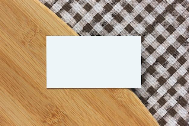 Carte de visite vide et planche à découper en bambou sur une nappe à carreaux, vue de dessus. table de cuisine. copie espace. maquette, créateur de scène.