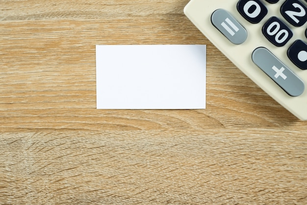 Carte de visite vierge ou carte de nom avec calculatrice sur bois