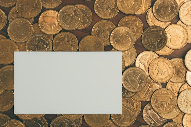 Carte de visite vierge ou carte de nom et pile de pièces de monnaie
