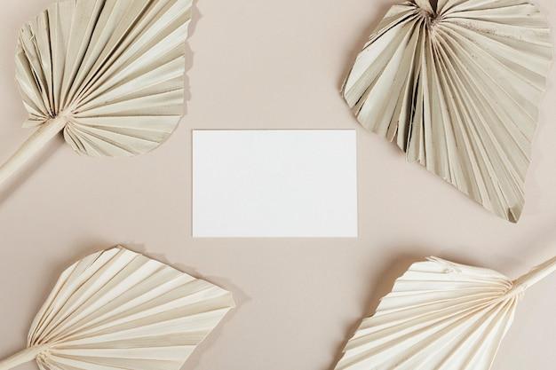 Carte de visite vierge avec des feuilles de palmier séchées