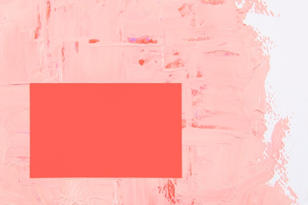 Carte de visite vierge, papier rose sur fond de peinture texturée