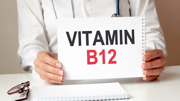Carte vitamine b12 entre les mains d'un médecin. médecin remet une feuille de papier avec texte vitamine b12, concept médical.