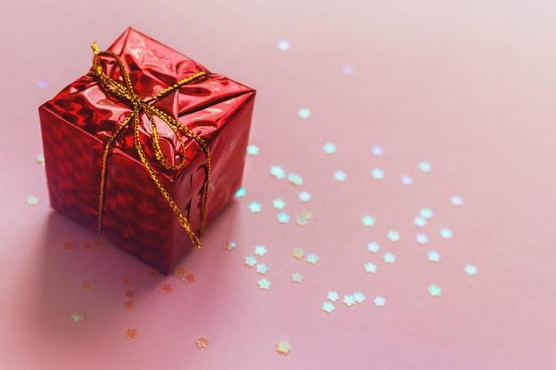 Carte de voeux d'anniversaire noël vacances. présenter un coffret rouge avec un ruban doré sur fond rose. fond de bokeh brillant paillettes brillantes. copyspace pour le texte