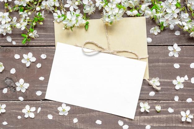 Carte de voeux blanc vierge et enveloppe avec branche de cerisier en fleurs au printemps
