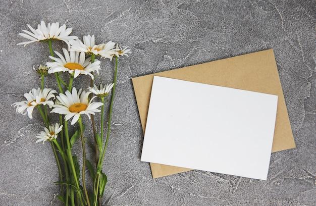 Carte de voeux blanche vierge et enveloppe avec des fleurs de camomille