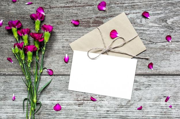 Carte de voeux blanche vierge et enveloppe avec des fleurs d'oeillets violets