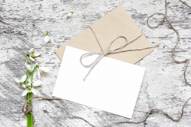Carte de voeux blanche vierge et enveloppe avec des fleurs de perce-neige