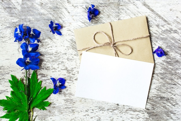 Carte de voeux blanche vierge et enveloppe avec des fleurs sauvages bleues