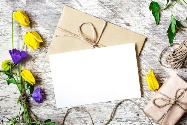 Carte de voeux blanche vierge et enveloppe avec des fleurs sauvages jaunes