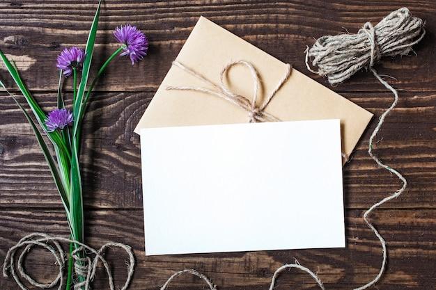 Carte de voeux blanche vierge et enveloppe avec des fleurs sauvages violettes