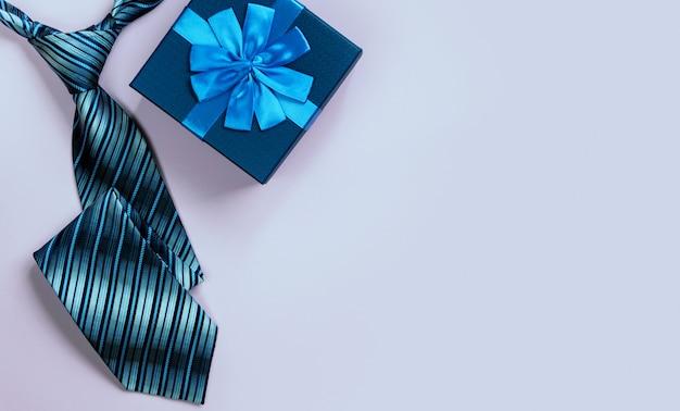 Carte de voeux avec boîte-cadeau décorée et cravate sur fond rose. vue de dessus.