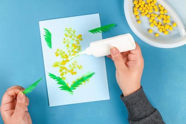 Carte de voeux bricolage avec des boules de papier fleurs mimosa pour le 8 mars sur fond bleu.