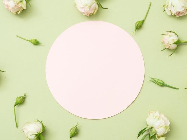 Carte de voeux. cercle sur fond vert. décor de roses blanches.
