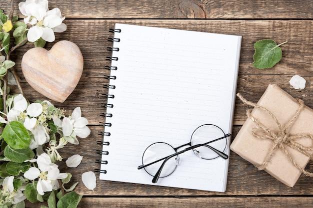 Carte de voeux avec coeur, cadeau, fleurs printanières et cahier vierge