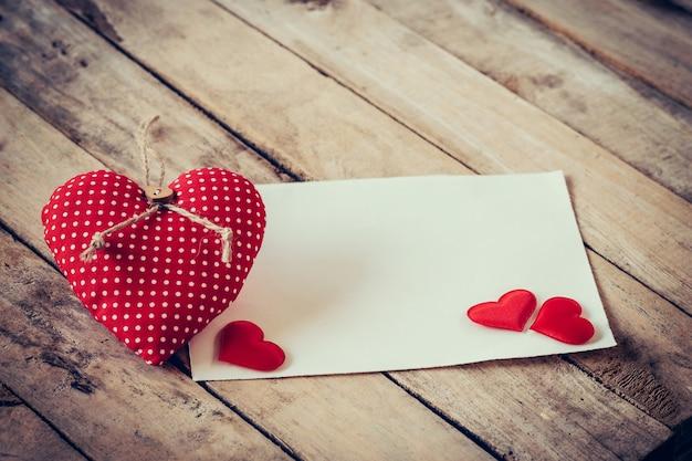 Carte de voeux et coeurs rouges avec de l'espace pour le texte sur fond de bois