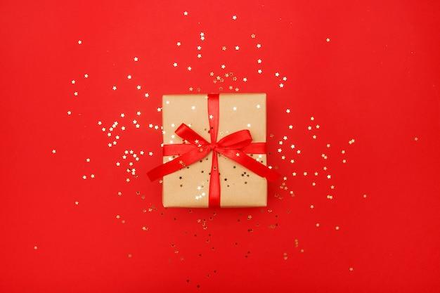 Carte de voeux de composition de noël. cadeau de papier kraft sur fond rouge