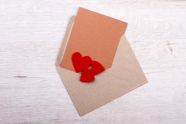 Carte de voeux sur enveloppe. coeurs en tissu sur carte postale. l'amour est dans l'air. soyez heureux en vacances.