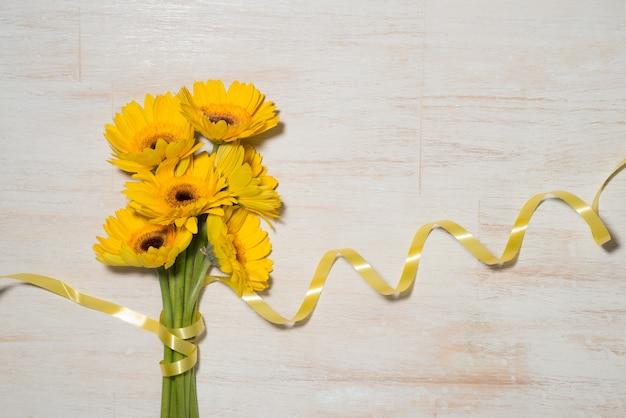 Carte de voeux avec des fleurs jaunes sur fond en bois. vue de dessus avec espace de copie