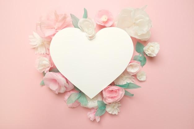 Carte de voeux avec des fleurs en papier sur rose