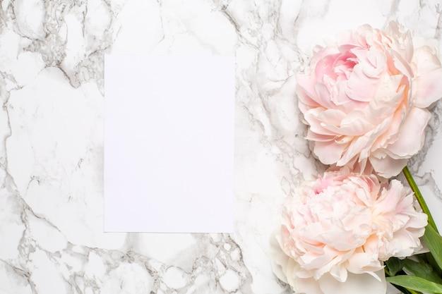 Carte de voeux et fleurs roses pivoine sur une surface de marbre. article de vacances et d'été.