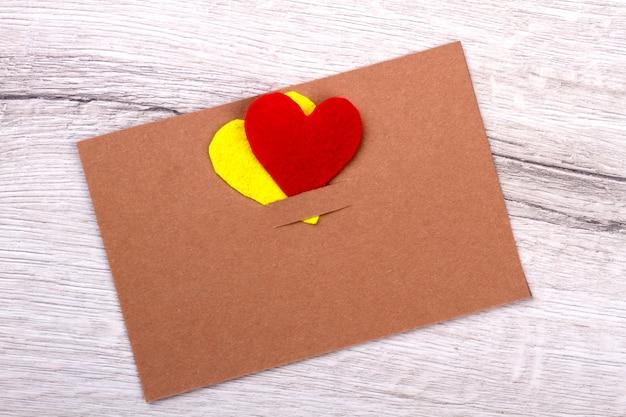 Carte de voeux sur fond en bois. carte papier avec coeurs. préparez vous-même un cadeau. idées pour le fait main.