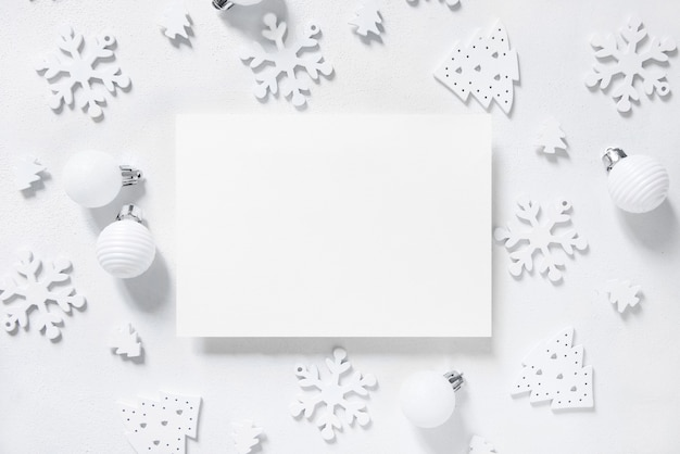 Carte de voeux horizontale vierge avec vue de dessus de décorations de noël blanches sur tableau blanc. composition d'hiver avec enveloppe mockup, espace de copie