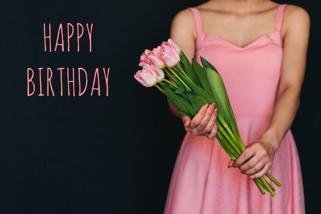 Carte de voeux avec l'inscription joyeux anniversaire. bouquet de tulipes roses dans les mains