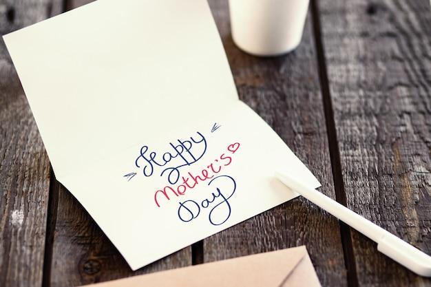 Carte de voeux d'invitation vierge pour remplacer votre conception sur une table en bois grise. concept de bonne fête des mères