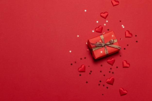 Carte de voeux de joyeuses fêtes avec des confettis d'étincelles paillettes d'or avec boîte-cadeau sur fond rouge.