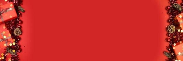 Carte de voeux de joyeuses fêtes avec des guirlandes brillantes, des coffrets cadeaux et des boules sur fond rouge avec espace de copie